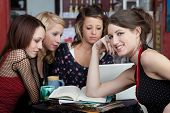 stock photo of foursome  - Attractive young lady in a cafe with friends - JPG