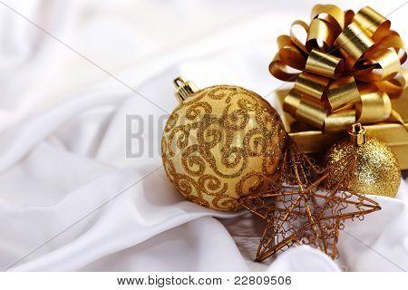 gold christmas ball on white silk