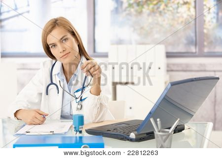 Attractive female doctor sitting at desk in office writing report, smiling.?