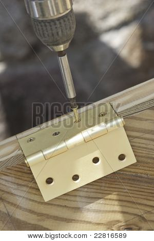 Builder Fitting A Brass Hinge To A Door