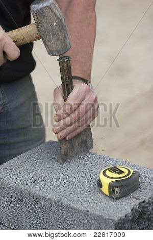 Builder Cutting A Breeze Block