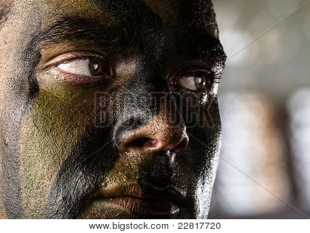 young soldier face with jungle camouflage, outdoor