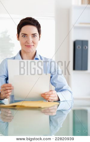 Portrait of a Businesswoman sitting behind a desk with papers in an office