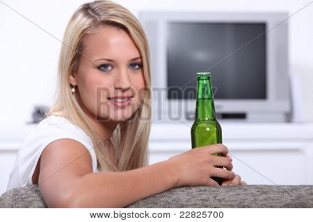 Young woman at home with a bottle of unopened lager