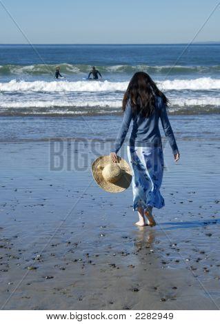 Mujer caminando hacia el océano