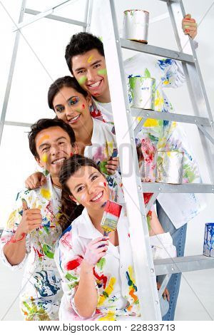 Group of painters holding their brushes and smiling on a ladder