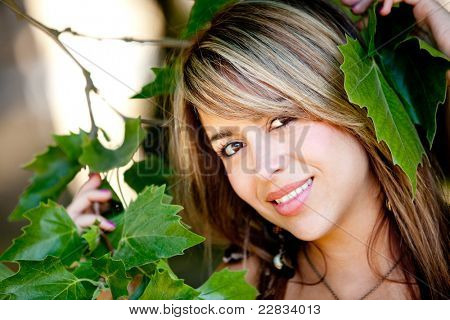 Beautiful woman portrait surrounded by leaves and nature ? outdoors