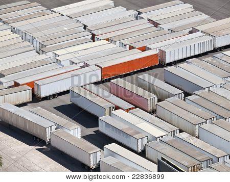Dozens of idle truck trailers in bright desert light.
