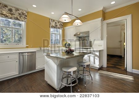 Kitchen with gold walls and white cabinetry