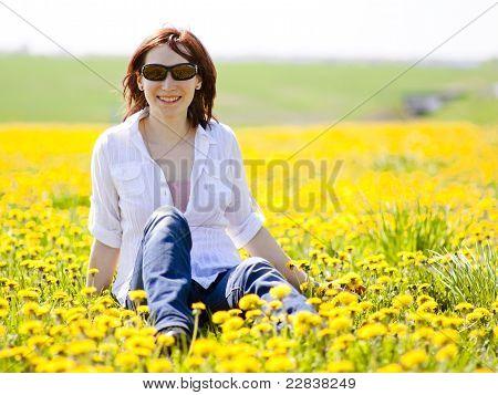 Woman is sitting in a beautiful meadow