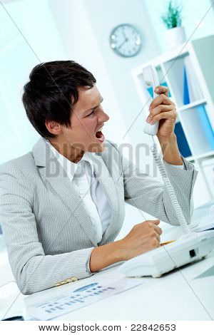 Image of annoyed boss losing her temper and screaming into phone receiver