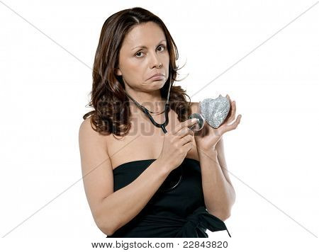 Portrait of displeased beautiful woman examining heart of stone with stethoscope isolated on white background