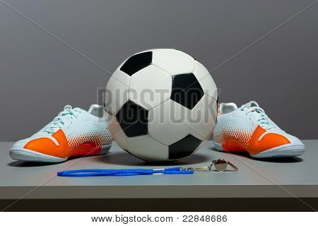 Sport concept - shoes, soccer ball and whistle.