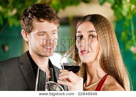 Couple at winetasting with red wine in a restaurant