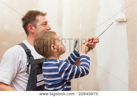 Father and son painting a wall in their home, they presumably do it in the course of moving in