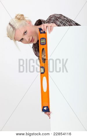 Woman with a spirit level and a board left blank for message or image