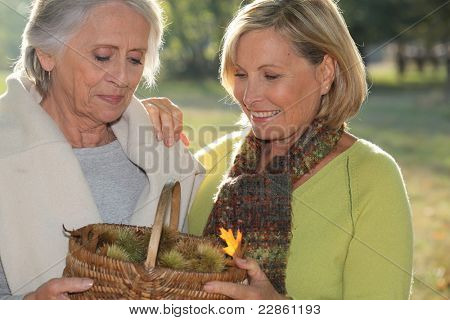 a mid age blonde woman and an older woman holding a wickerwork basket full of chestnuts