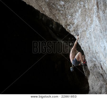 Young semi naked climber hanging on a rock without belay