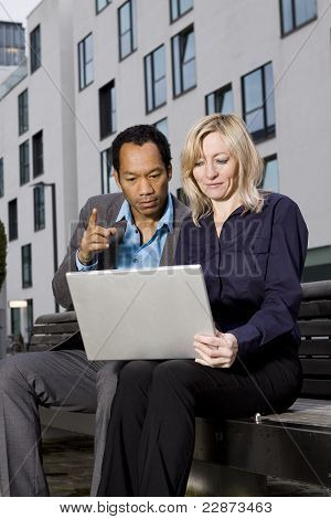 Business couple with notebook working outside