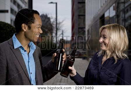 Business couple outside office drinking after work beer in a bottle
