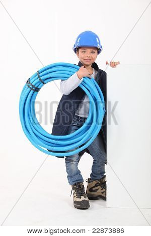 Young boy dressed as a plumber with a board left blank for your message