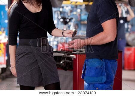 A customer in a mechanic shop deliver the car key