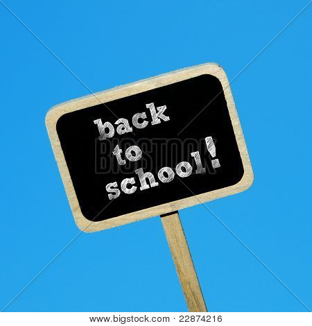 sentence back to school written in a blackboard label on a blu background