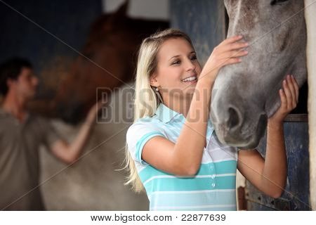 man and woman cuddling a horse