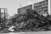 stock photo of katrina  - a pile of garbage after hurricane katrina in front of a hotel with an american flag in color on top - JPG