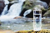 A Transparent Glass Glass With Drinking Mountain Water Stands In The Moss Stone On Sun Beame Against poster