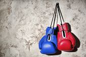Red and blue boxing gloves hanging on wall. Concept of political confrontation between American majo poster