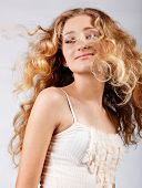 beautiful strawberry blond teenage girl with  long curly hair blowing in wind over grey studio backg