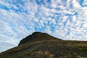 Beautiful Clouds Above Platafjellet In Summer. Svalbard. Rocky Hills With Blue Sky And White Clouds  poster