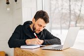 A Freelancer With A Laptop Writes A Note In A Notebook, Young Male Businessman Writing On A Notepad  poster
