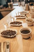Close Up View Of Arranged Bowls With Coffee Beans And Grind Coffee For Food Function On Wooden Table poster