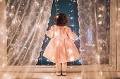 Cute Child Girl Stay Near The Window And Looking At The Stars. Little Kid Stay At Windowsill Around  poster
