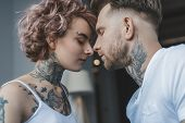 Young Tender Tattooed Couple Touching Noses With Closed Eyes poster