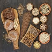 High fiber health food with whole grain bread, pasta, cereals and grains on an olive wood board and  poster
