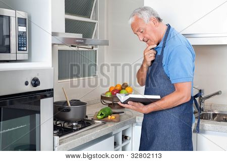 Senior man preparing food with the help of recipe book