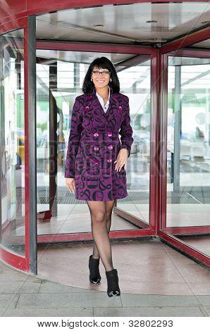 Pretty Woman In A Coat Going Thru Revolving Doors
