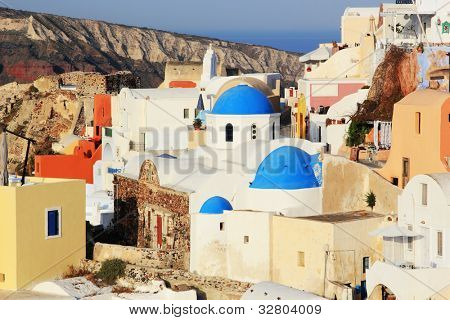 Traditional Greek white church arch with cross and bells with ferry boat passing by  in village Oia of Cyclades Island Santorini Greece