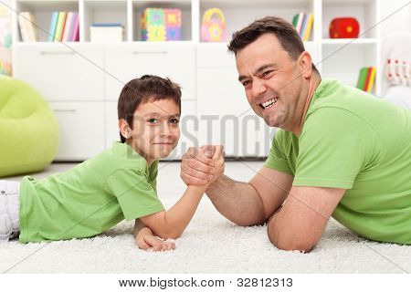 Happy father and son playing arm wrestling, lying on the floor