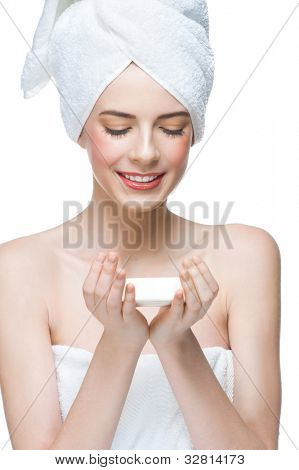 Portrait of young beautiful woman in white towel holding soap in her hands. Isolated on white background