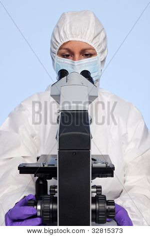 Photo of a biochemist looking at a laboratory microscope.