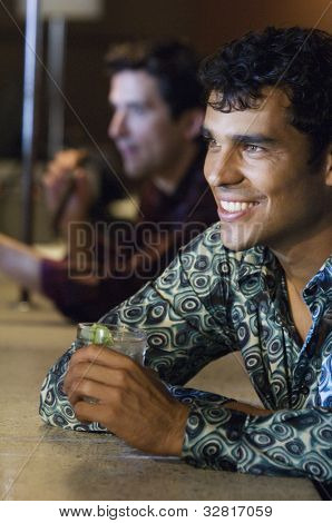 Hispanic man drinking at bar