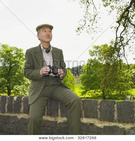 Senior Asian man holding binoculars