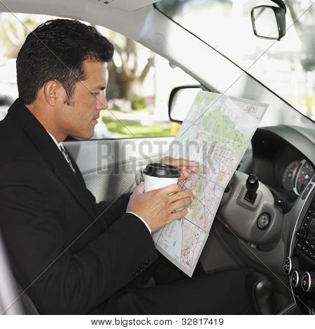 Hispanic man reading map in car