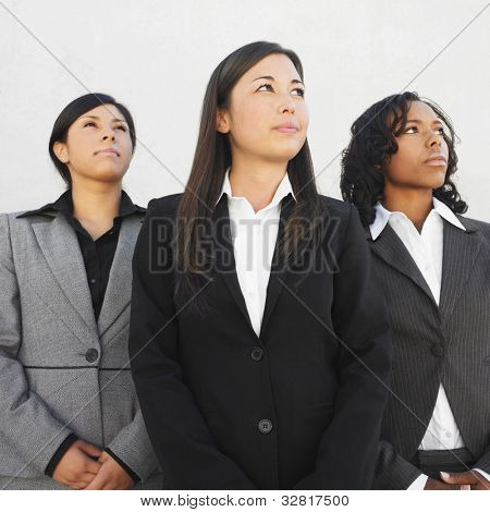 Multi-ethnic businesswomen looking up