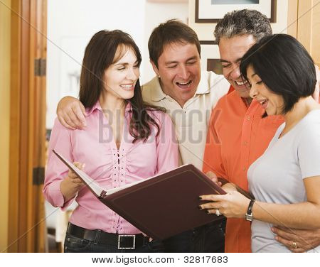 Two middle-aged couples looking at photo album