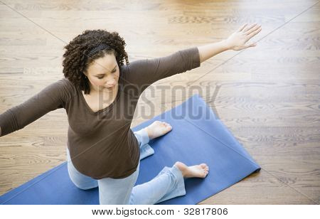 Pregnant African woman practicing yoga